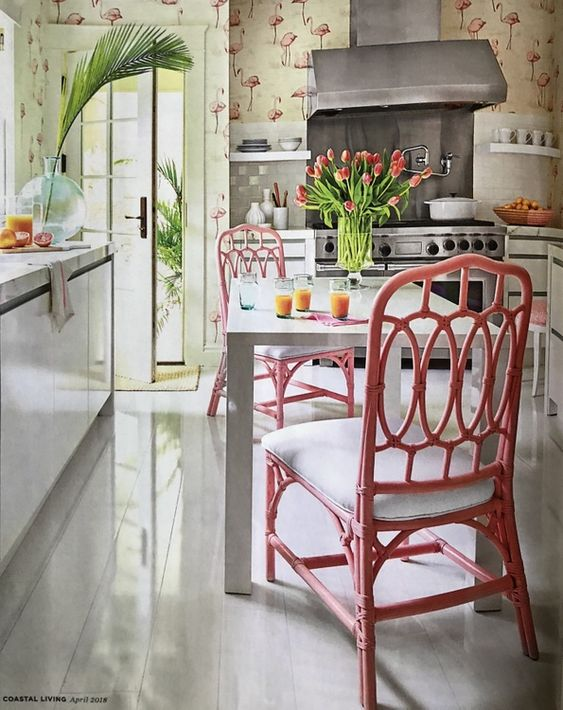 pink rattan chair with white cushion, white table, white bottom cabinet with marble kitchen top, pink flamingo wallpaper, whtie bottom cabinet, silver hood