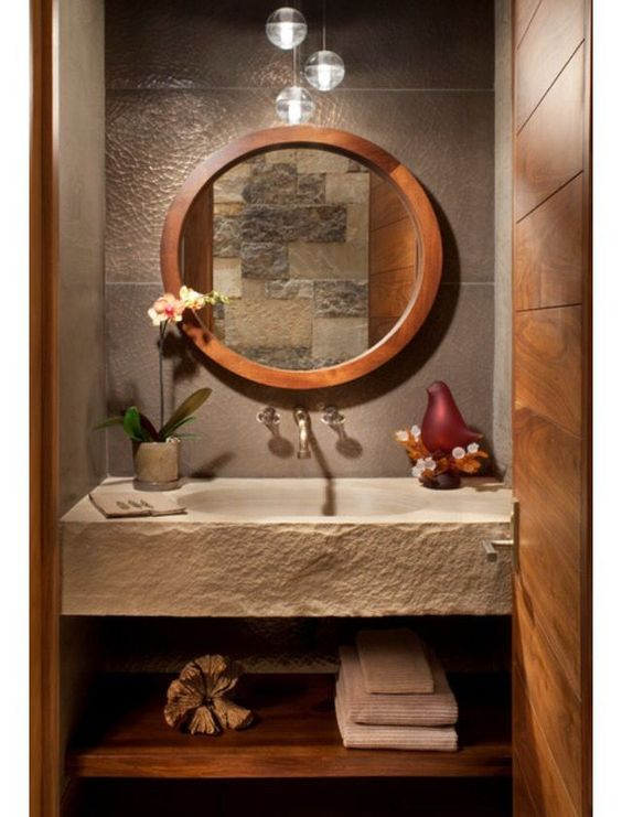powder room, brown wall tiles, cemented floating sink, wooden shelves under, wooden framed round mirror