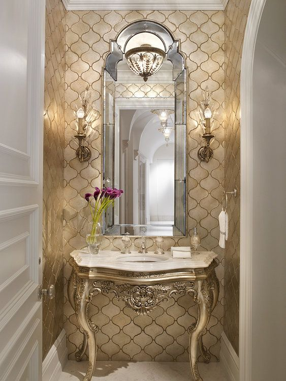 powder room, golden wallpaper accent wall, mirror framed mirror, golden table vanity with details, marbled top, sconces