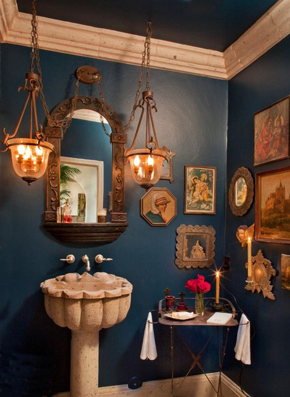 powder room, navy wall, classic pictures on the wall, stone cement sink, copper framed mirror, glass pendants, table