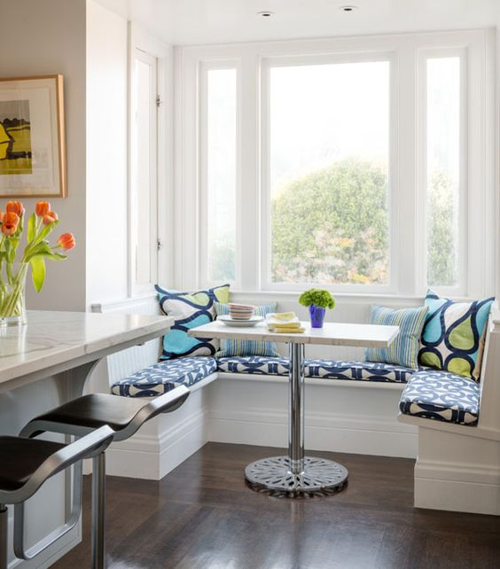 small banquette, dark wooden floor, white bench along the window, rectangular table, blue patterned cushion, pillows