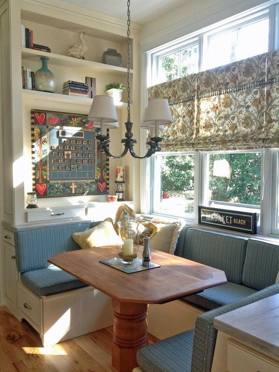small banquette, white built in bench, blue cushione, wooden table, white covered chandelier, flowery patterned shade, built in shelves