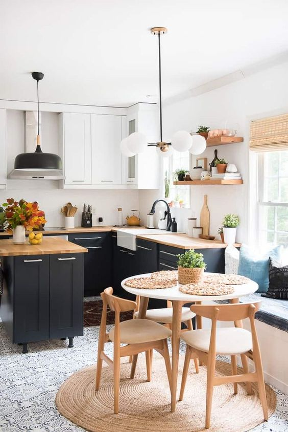 small kitchen, patterned floor, black bottom cabinet, white upper cabinet, wooden kitchen top, dining set with white table, wooden chairs, rattan rug