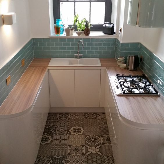 small kitchen, patterned floor tiles, white wall, green subway backsplash, wooden top, white bottom cabinet, white sink