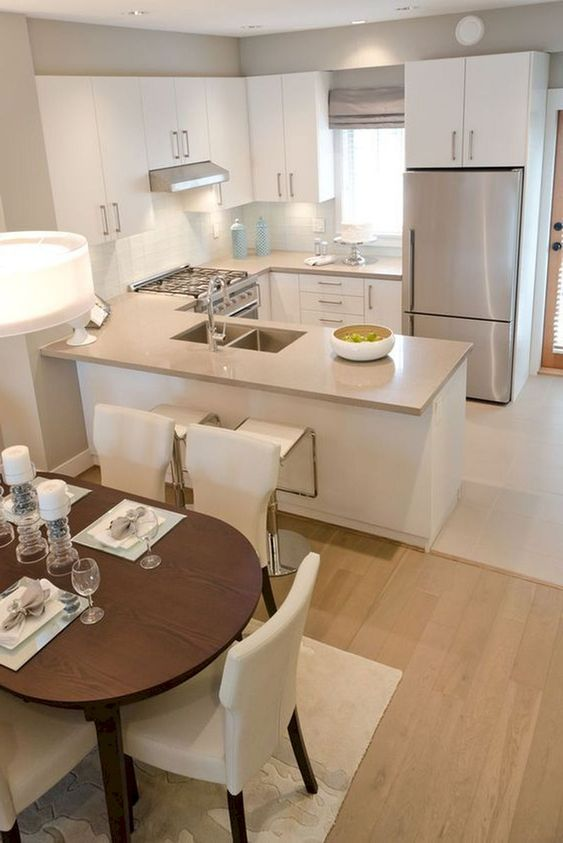 small kitchen, white floor, white bottom cabinet, white upper cabinet, silver fridge, dining set with dark wooden table, white chairs