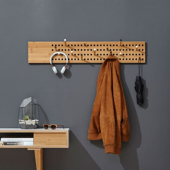 small wooden pegboards, wooden table, grey wall