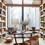 Study Room With Rattan Rug, Wooden Shelves, Wooden Table, Wooden Chair With Rattan Seating, White Table Lamp, Large Window