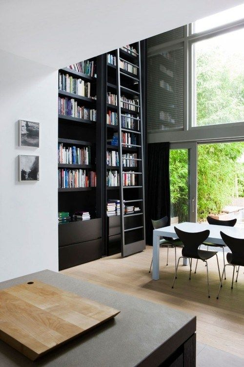 tall black built in book shelves with stairs, wooden flor, white table, black chairs, tall glass window