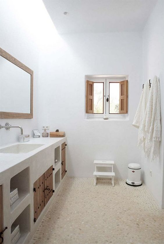 white bathroom, white plaster vanity with built in shelves, wooden drawers, wooden door, long mirror, wooden window, white stool, brown floor, white stool