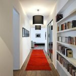 White Built In Bookshelves On The Alley, Wooden Floor, Red Rug, Black Pendants
