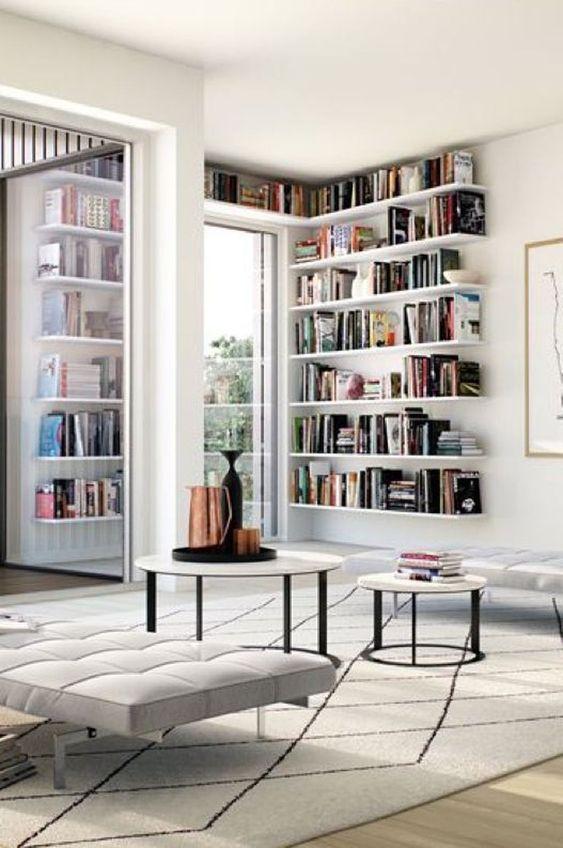 white corner bookshelves, wooden floor, white bench, round nesting table