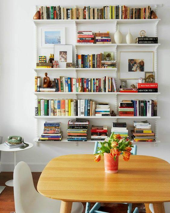 white floating bookshelves, white side table, wooden table, white chair