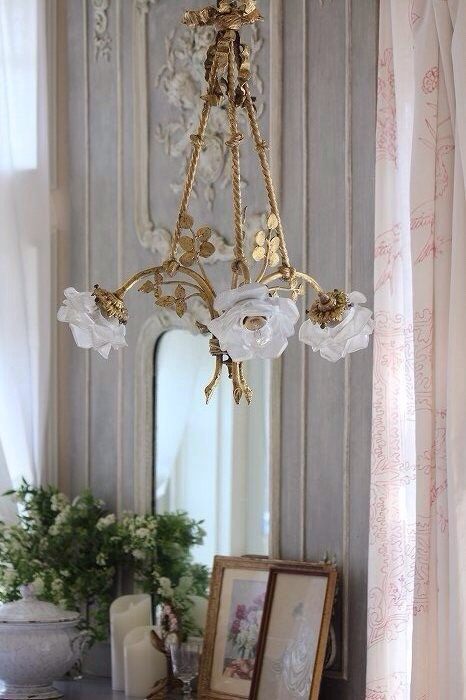 white flower on the chandelier, pink curtain, detailed wall, mirror, wooden frames