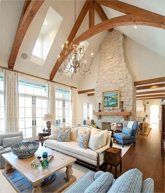 white vaulted ceiling, wooden triangle beams, wooden floor, blue chairs, white sofa, white wooden coffee table, white curtain, chandelier, wooden shelves