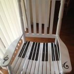 White Wooden Chair With Piano Keys Painted On The Seating, G Clef And F Clef On The Arm Rest