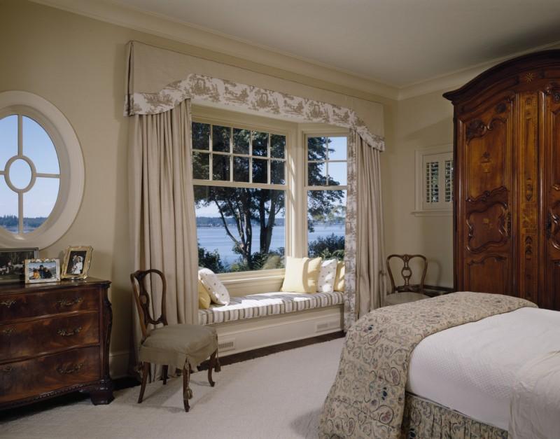 window valance beige walls windows window bench wooden chairs wooden wardrobe wooden dresser bed patterned bedding pillows curtains