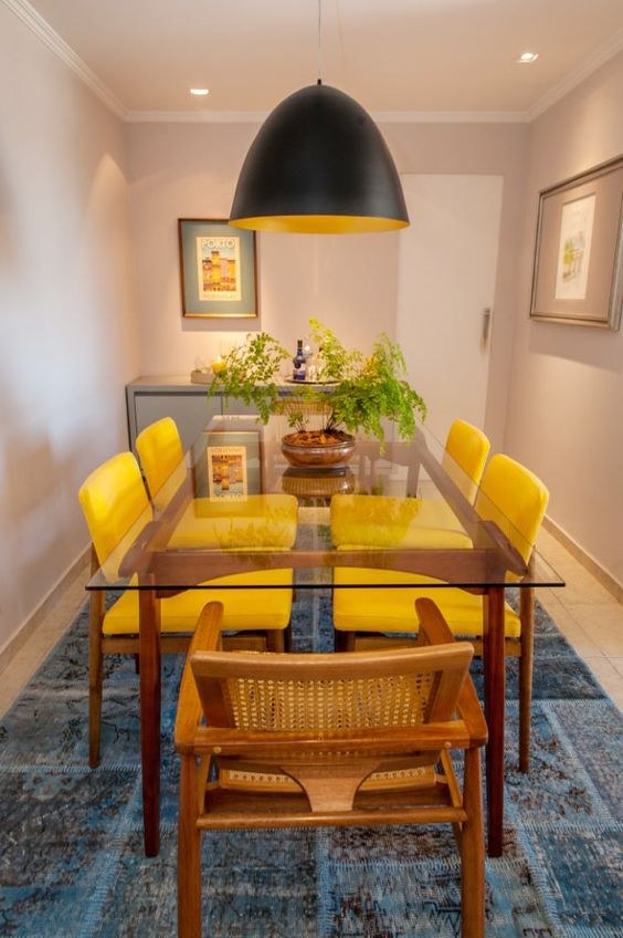 wooden chair with rattan back, yellow chair, blue rug, beige wall, black pendant with yellow inside
