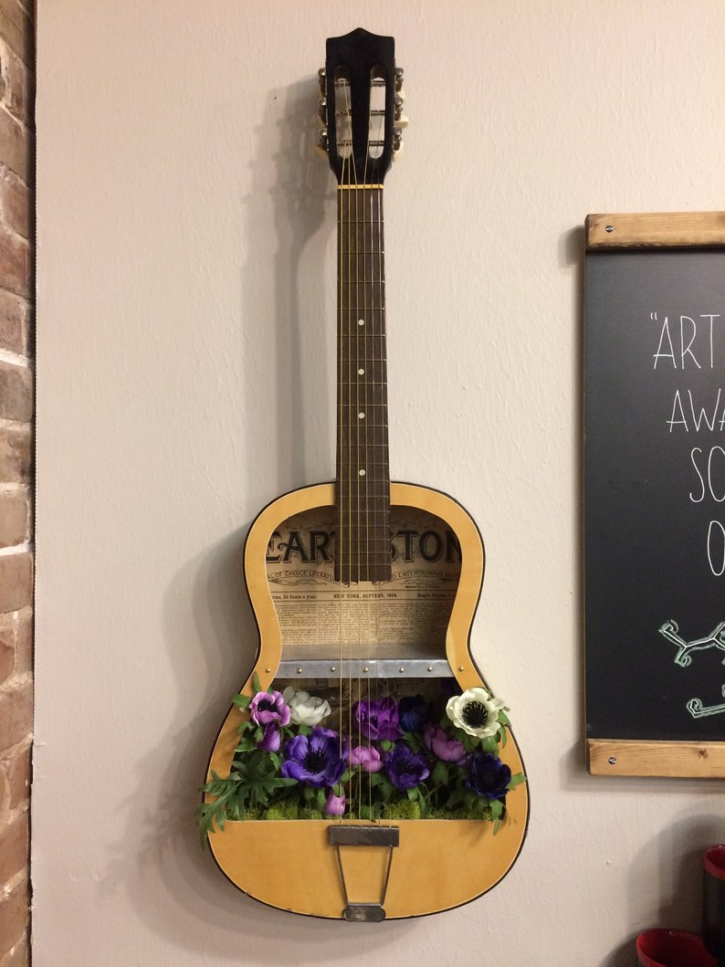 wooden guitar decoration with flowers inside, beige wall