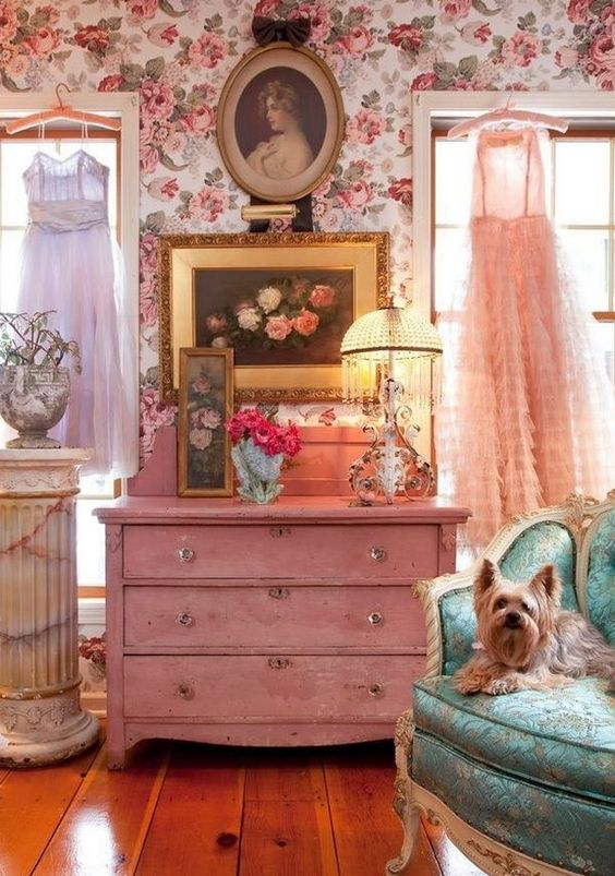 a room, wooden floor, pink shabby cabinet, pink flower wallpaper, white framed window, shabby table lamp, turquoise chair with white classic frame