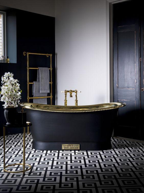bahtroom, white wall, black wall, black tub with golden inside, black wooden door, black white patterned floor. black side table, goden rack