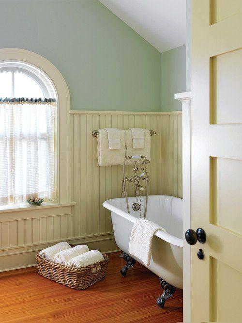 bathroom under the slope, wooden floor, blue wall, white wainscoting, white tub, white framed window