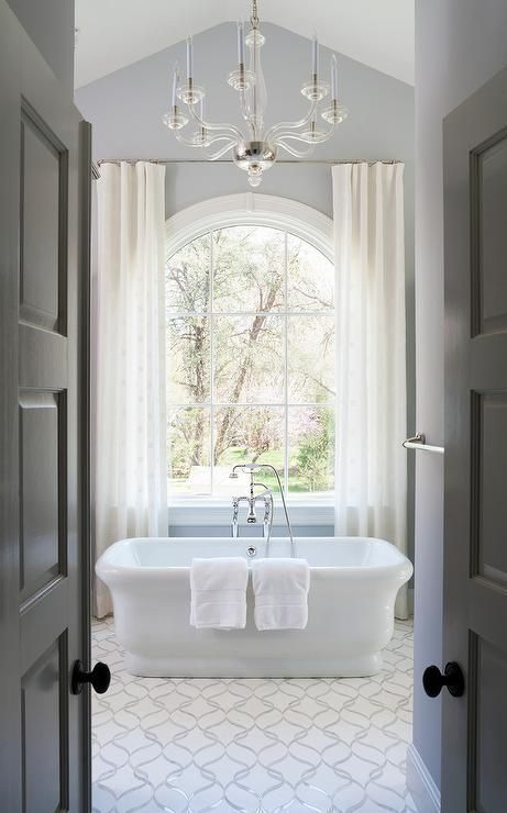 bathroom, white subtle patterned tiles, grey wall, chandelier, white tub, whtie curtain, chandelier