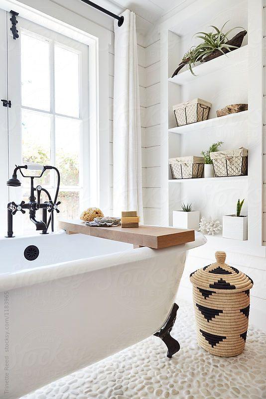 bathroom, white wooden built in shelves, white wooden plank wall, white tub, white stone floor, white framed window, rattan basket