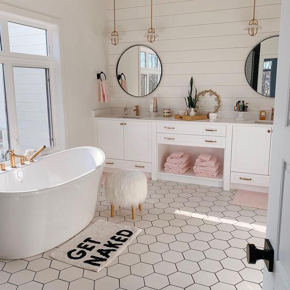 bathroom, whtie wall, white plank wall, white cabinet, white tub, white hexagonal floor tiles, round mirror
