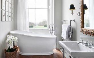 bathroom, wooden floor, white wall, arch window, white tub, white sink, golden framed mirror
