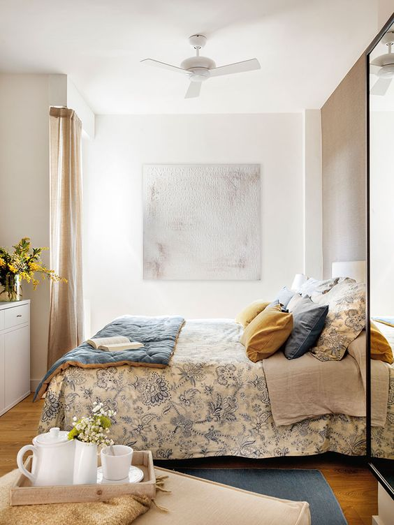 bedroom, wooden floor, white wall, white ceiling fan, blue patterned bedding, blue rug, white cabinet, tall glass window