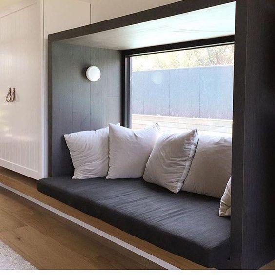 black box window seat, wooden floor, black cushion, white cabinet, white pillows