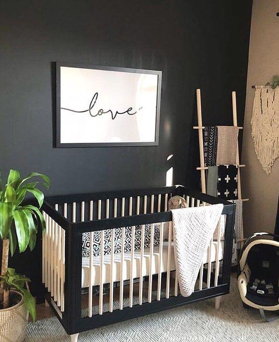 black framed baby crib, white fence, white cushion, white rug, wooden floor, black wall, wooden rack