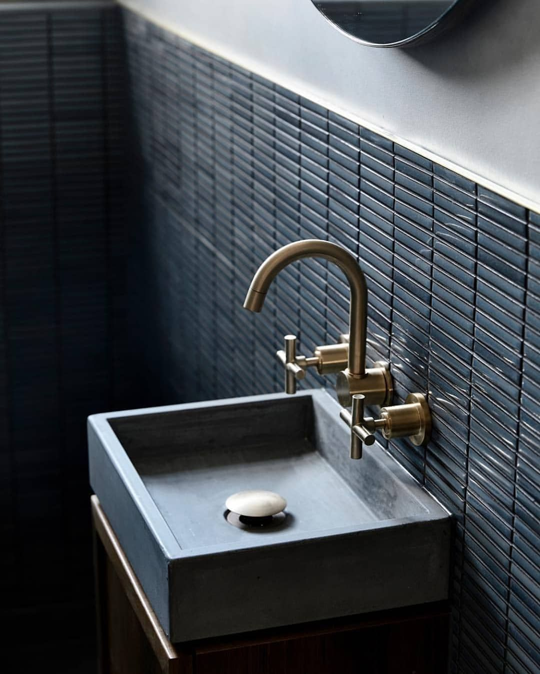 black horizontal lines backsplash, grey wall, grey square sink, golden faucet, wooden cabinet