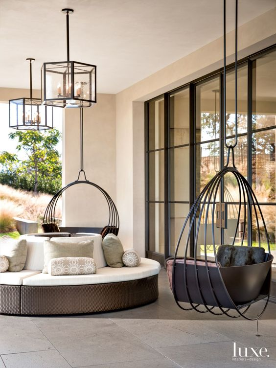 black ring round metal with black seating on the terrace, white round sofa, glass covered chandelier