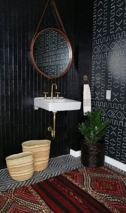 black vertical long tiles, white cloating sink, black white patterned floor tiles, black patterned wall, red rug, round wooden mirror