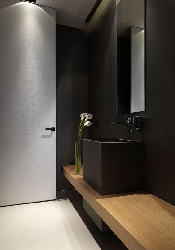 black wall, wooden floating vanity, black tal square sink, black faucet, mirror, beige floor
