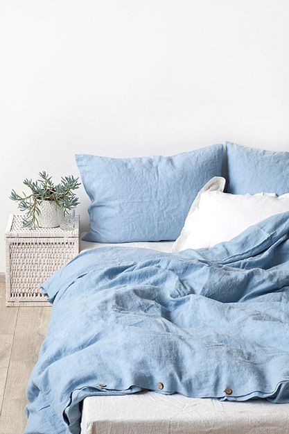 blue bedding, wooden floor, rattan side table