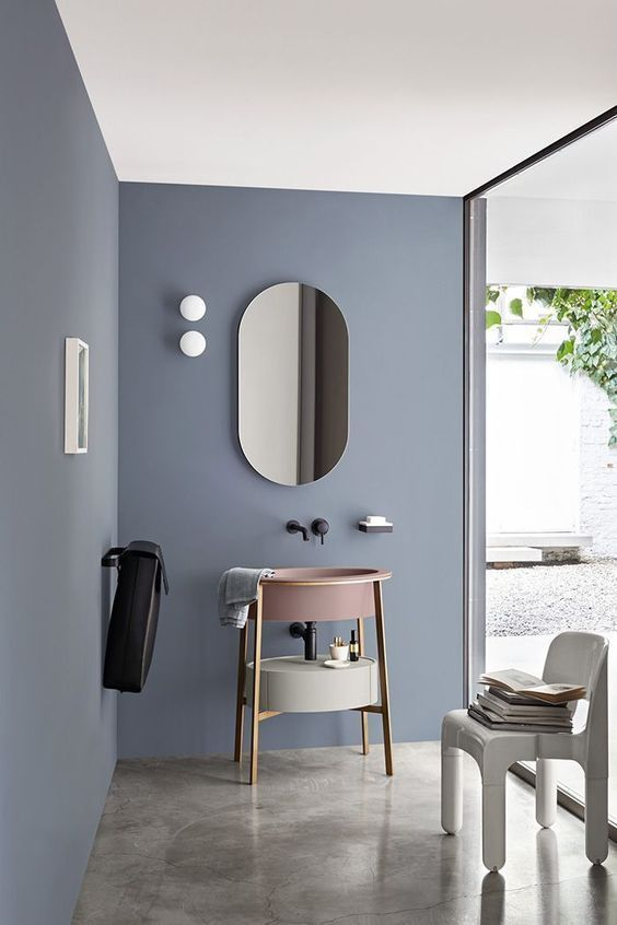 blue wall, seamless floor, round shelves vanity, mirror, white chair, clear glass wall