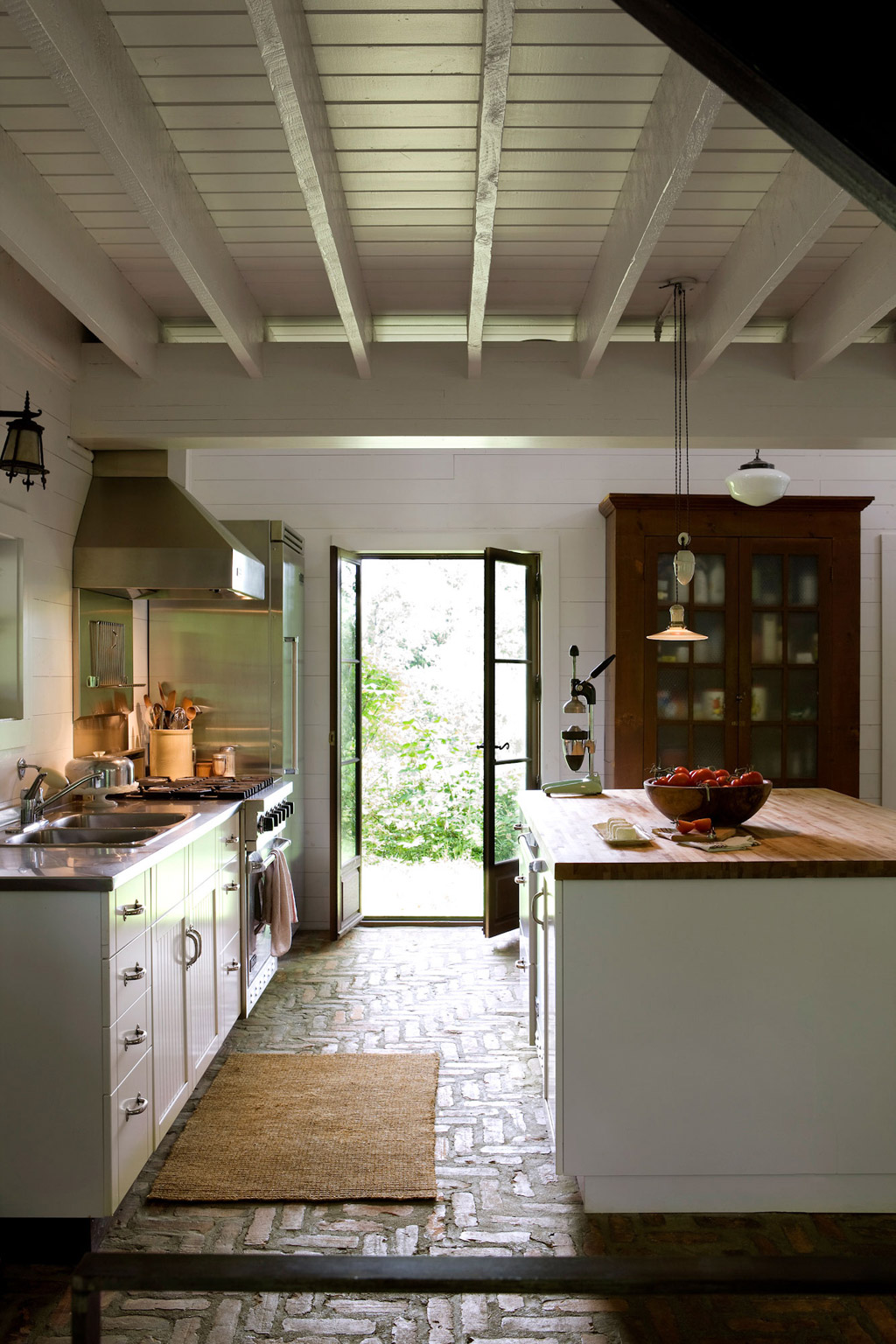 brick floor in the ktichen, white cabinet, white island, wooden top, white wooden ceiling and beams