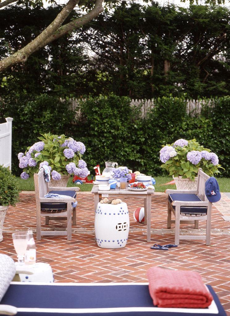 brick herringbone floor in the atio, wooden dining set with bench, indigo bed, plants