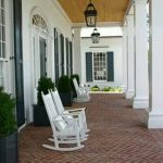 Brick Herringbone Floor On The Front Terrace, White Wall, Wooden Ceiling, Classic Pendant, White Rocking Chairs, White Posts