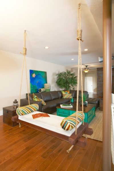 brown board swing, white cushion, colorful striped pillows, wooden floor, rattan rug, leather sofa, green coffee table