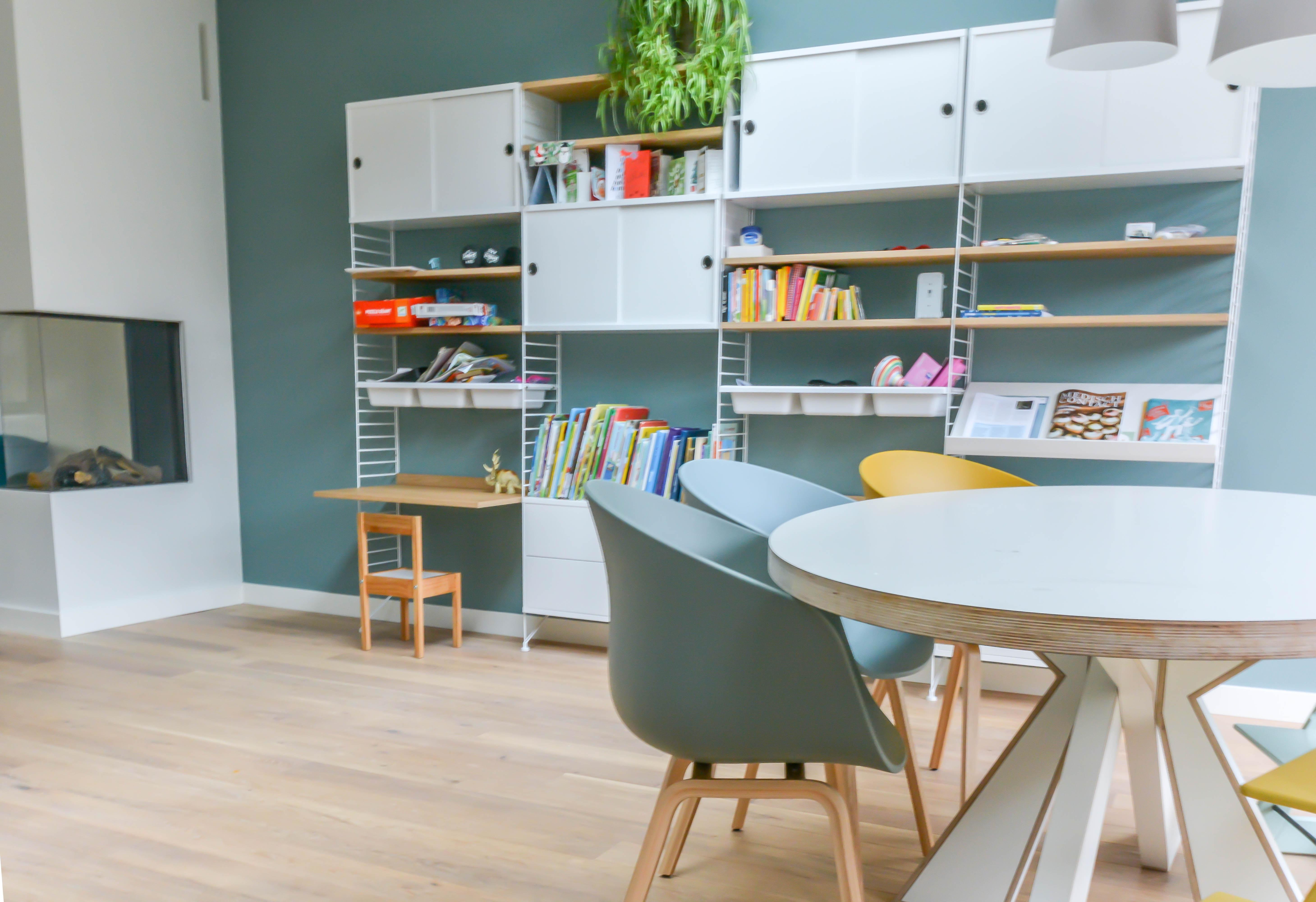 children study room, wooden floor, green wall, dining set, white shelves, floating table on the shelves, wooden stool