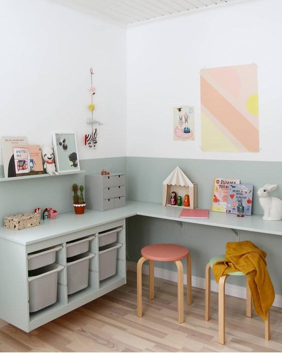 children study room, wooden floor, white wall, soft green wall and table set with shelves, pink green stool