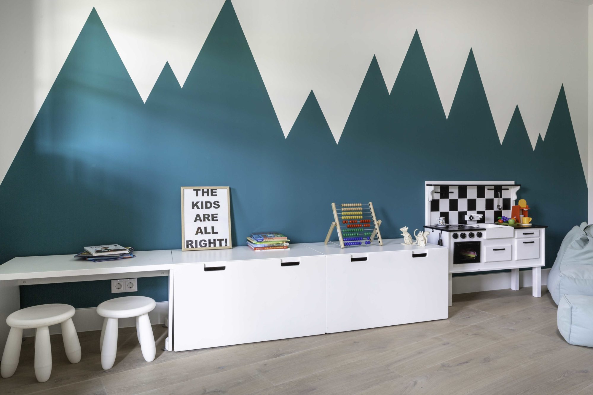 children study, wooden floor, white storage with white top, white table, white low stools, white wall with green mountain shadow paint