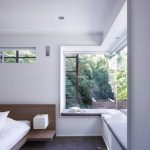Clear Glass On The Corner Of A Bedroom, Window Nook, Grey Cushion, Dark Floor, Wooden Bed Platform