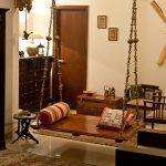 Dark Brown Board Swing, Detailed Rail, Red Pillows, In The Middle Of The Room, White Wall,