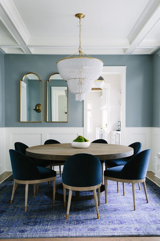 dining room, wooden floor, soft green wall, white wainscoting, crystal chandelier, round wooden table, blue chairs, purple rug