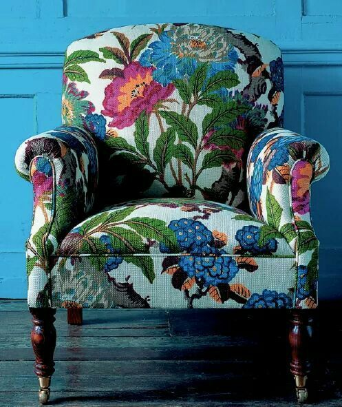 flowery patterned chair, woden floor, blue wall