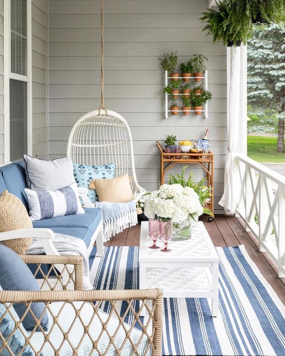 front porch, wooden floor, blue striped rug, white plank wall, blue sofa, blue pillows, rattan chairs, white rattan swing, white coffee table